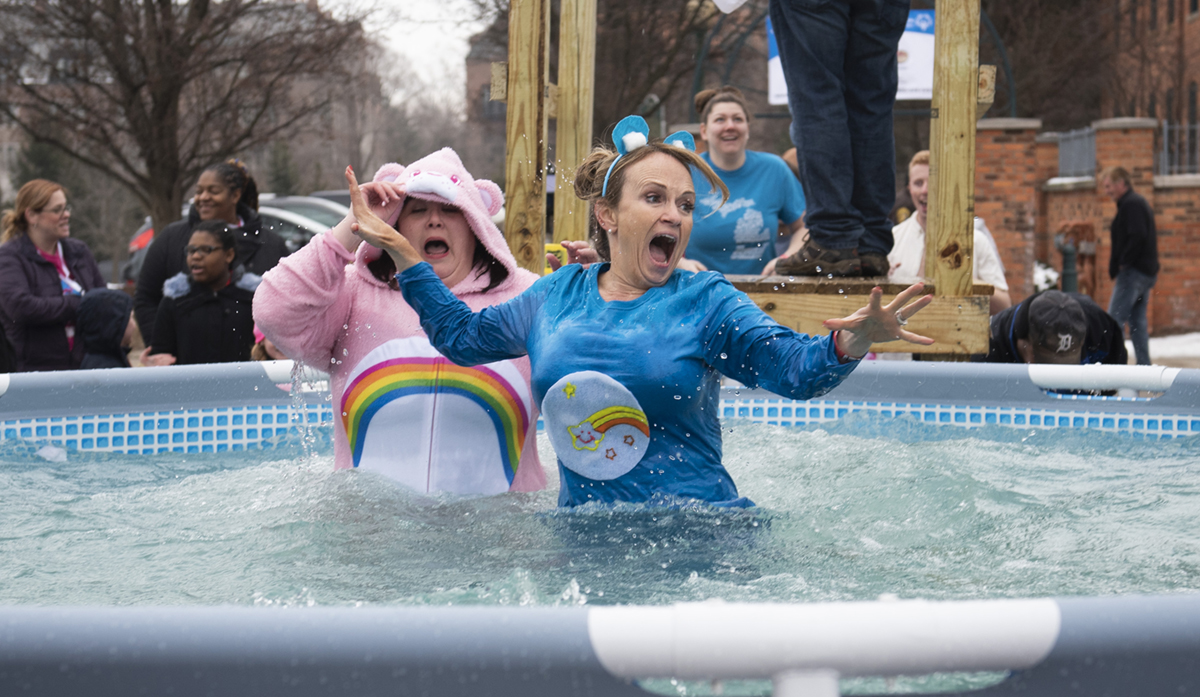 Plungers react to hitting the icy water at a Polar Plunge