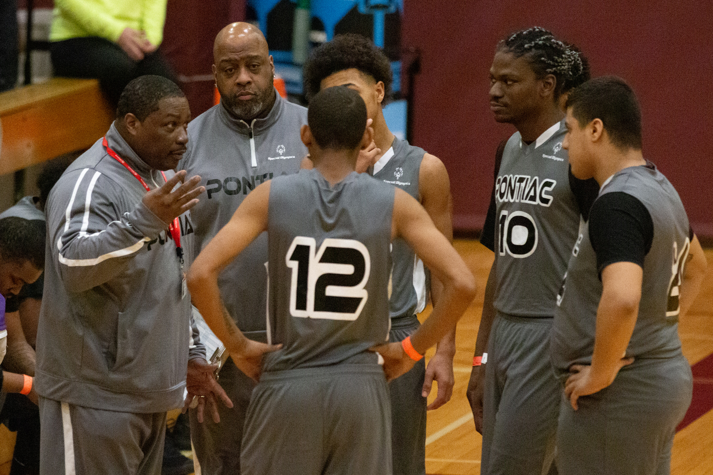 A basketball team huddles around its coaches during a timeout.