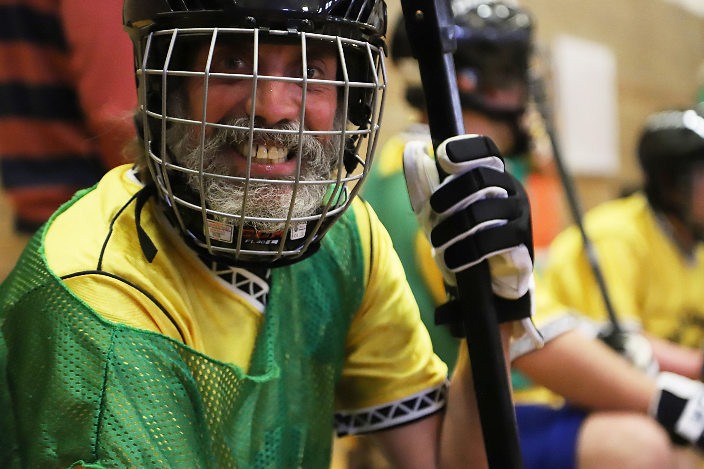 A Special Olympics athlete wearing a hockey mask smiles