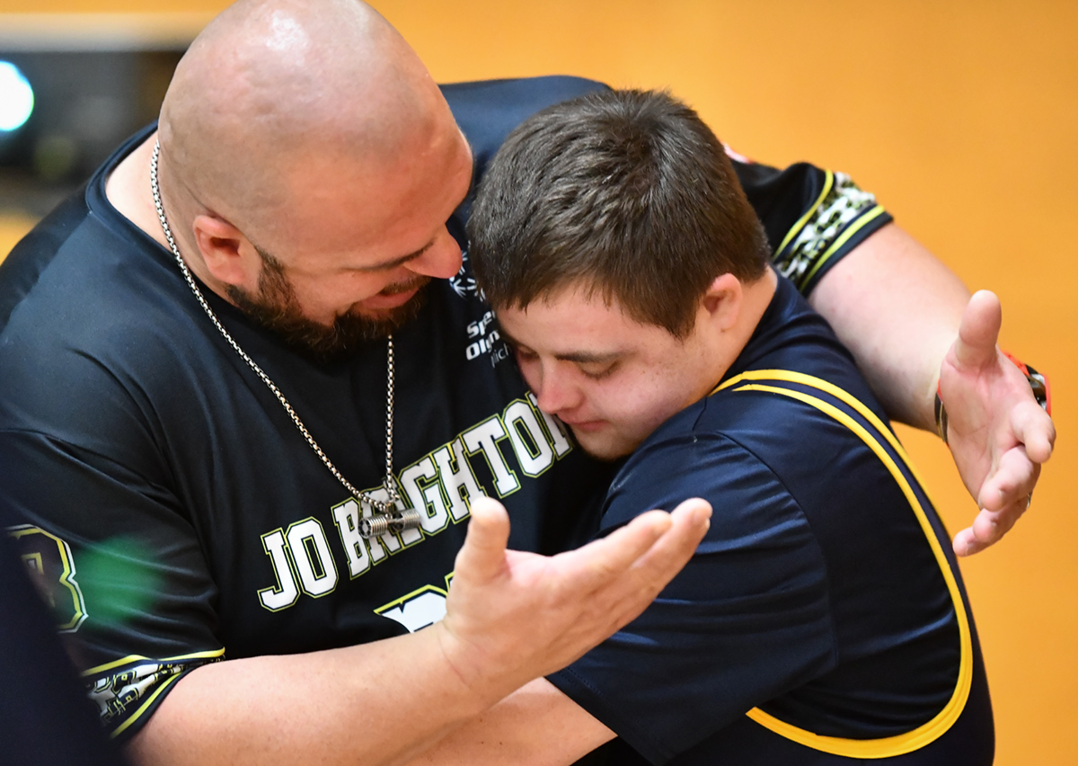 An athletes gets a hug from a powerlifting coach