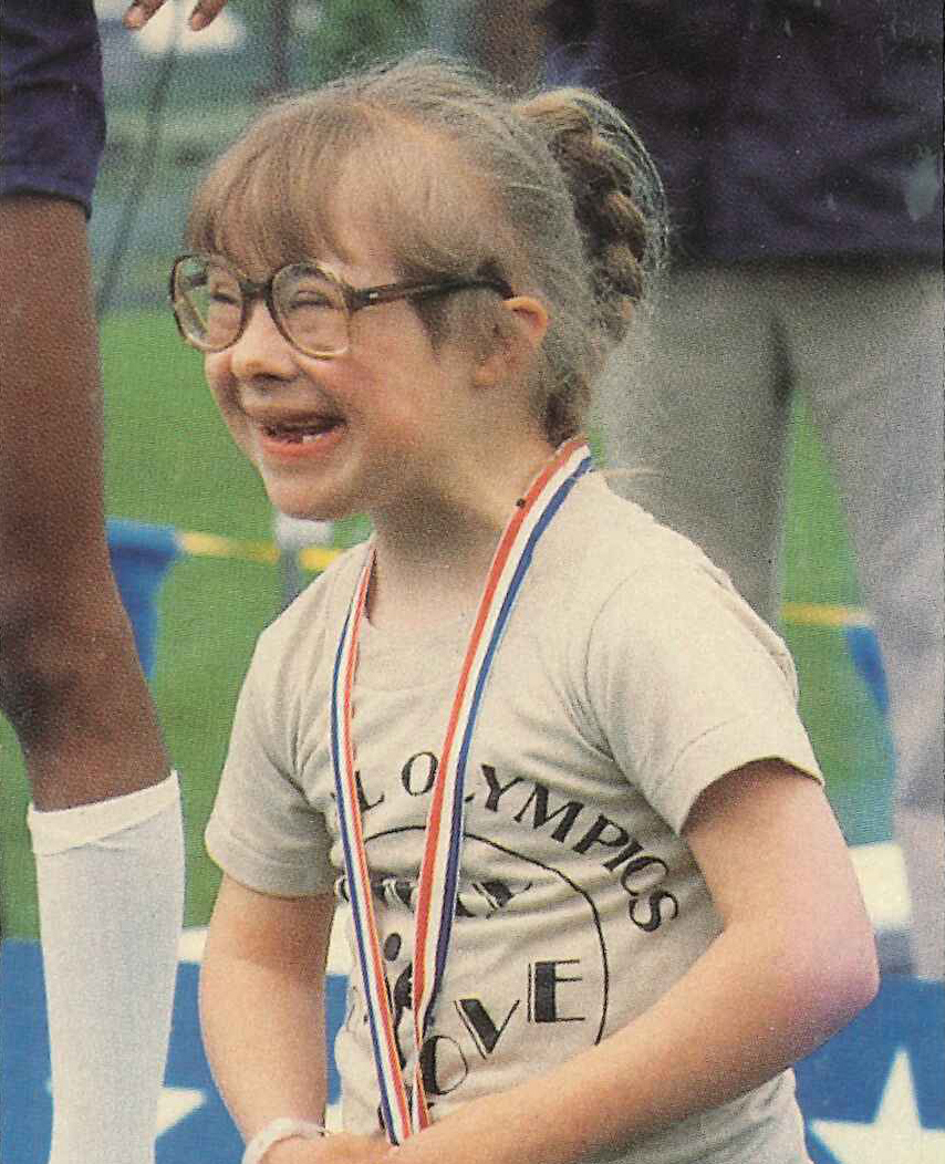 A young Special Olympics Michigan athlete smiles with a medal around her neck.
