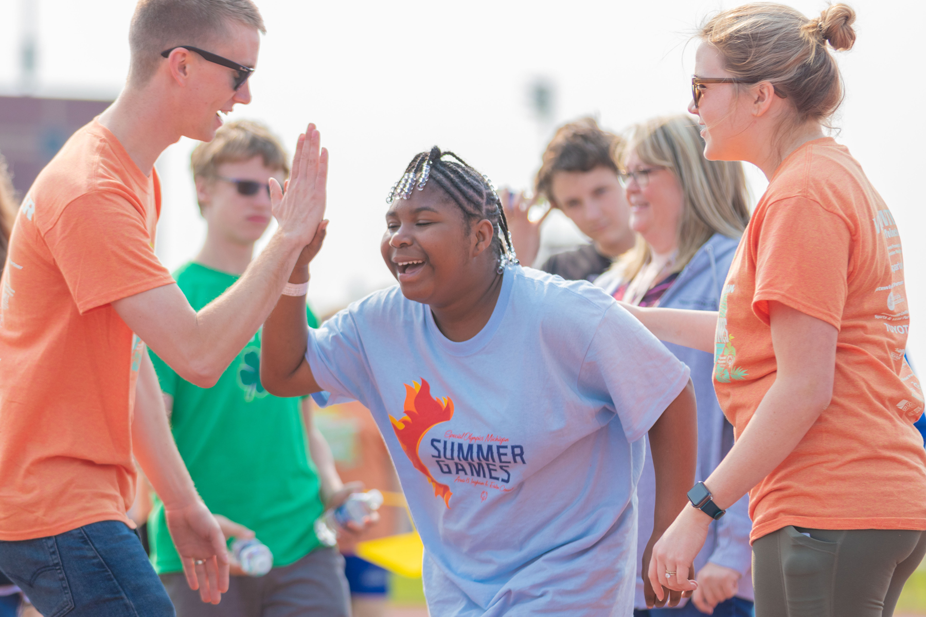 Volunteers congratulate a Special Olympics Michigan athlete.
