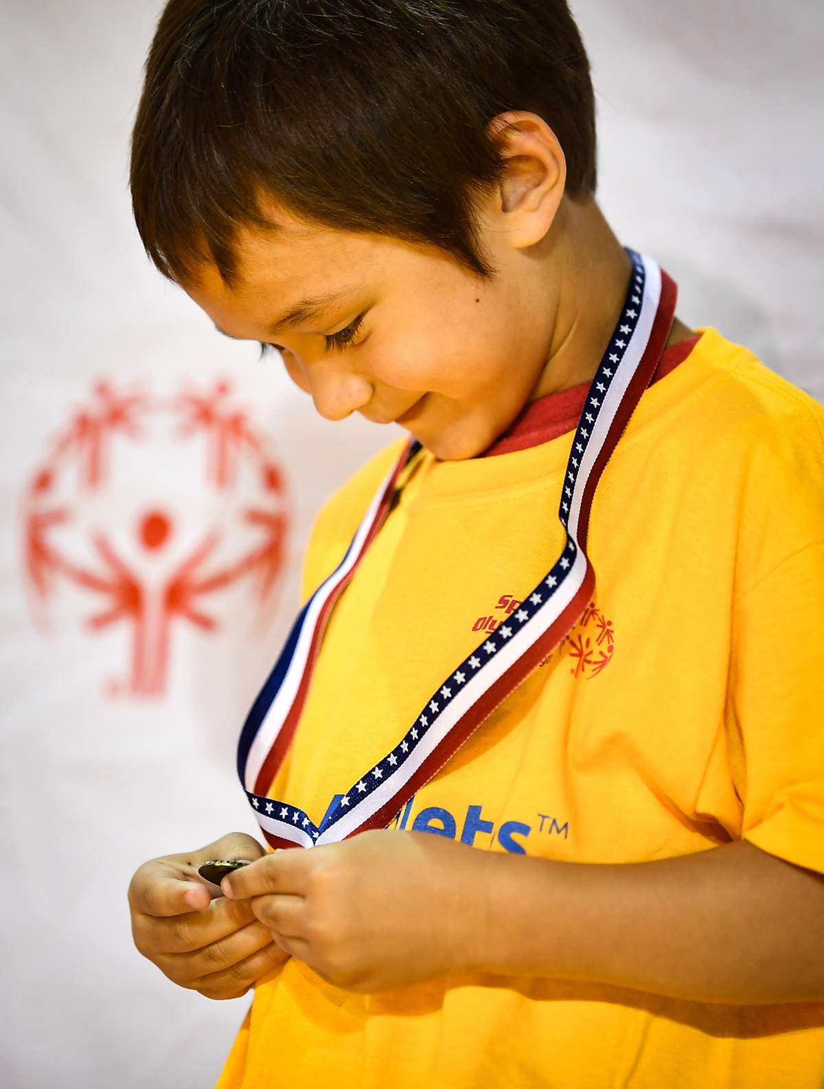 A Young Athlete admires his medal.
