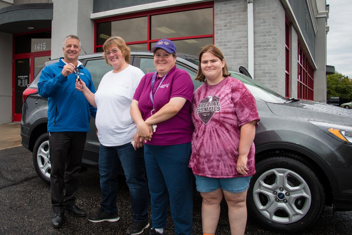 Raffle winner Teresa Carlson receives the keys to her brand new Ford Escape.