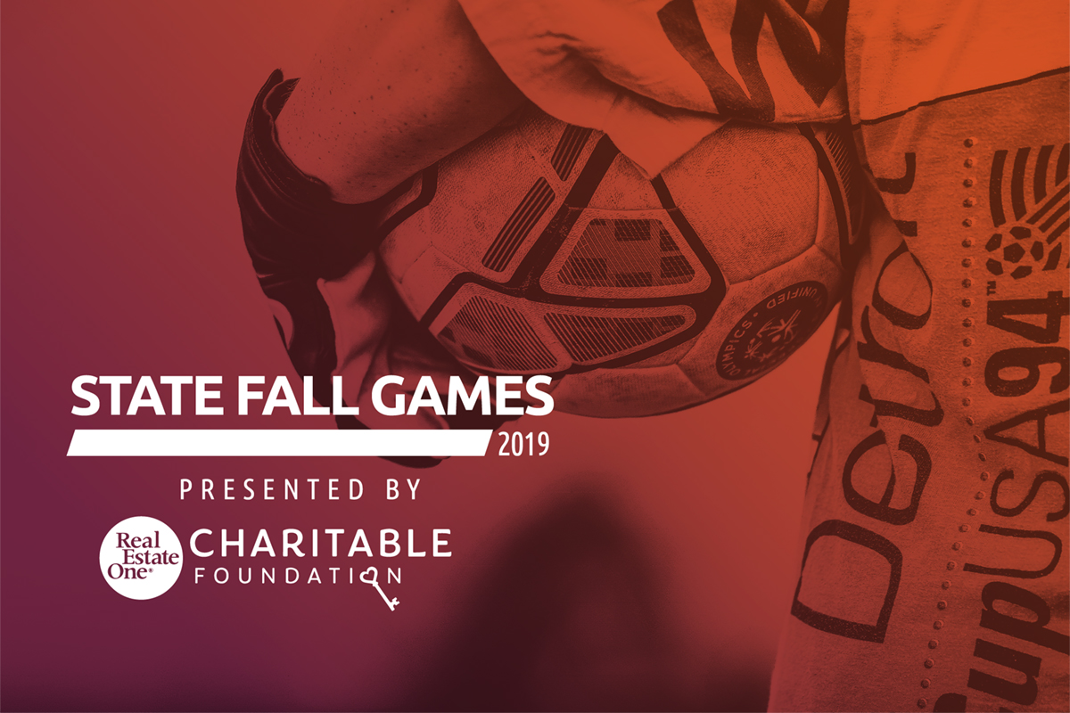 Closeup of a soccer ball being held by an athlete with the words State Fall Games presented by Real Estate One Charitable Foundation