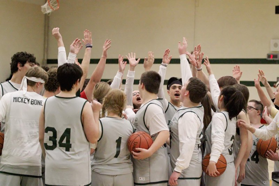Howell High School Students huddle up during a basketball game