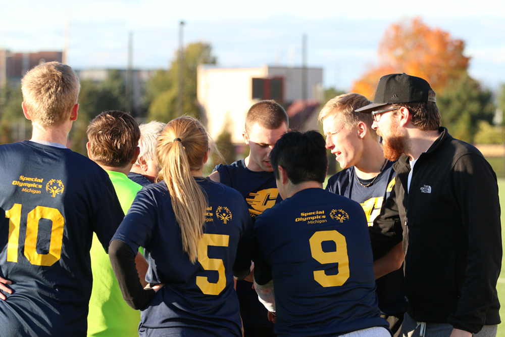 SO College participants huddle during a Unified soccer game.
