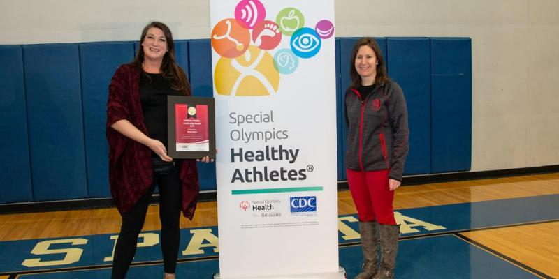 Renne Wyman and Heather Burke stand in front of a Healthy Athletes bannger