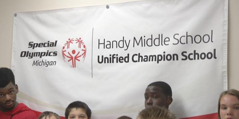 Handy Middle School students stand near a Special Olympics banner
