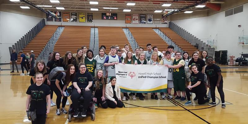 Students at Howell High School pose with a Unified Champion Schools banner.