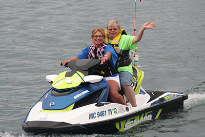 A Special Olympics Michigan athlete receives a ride on a personal watercraft from a Water Warriors member.