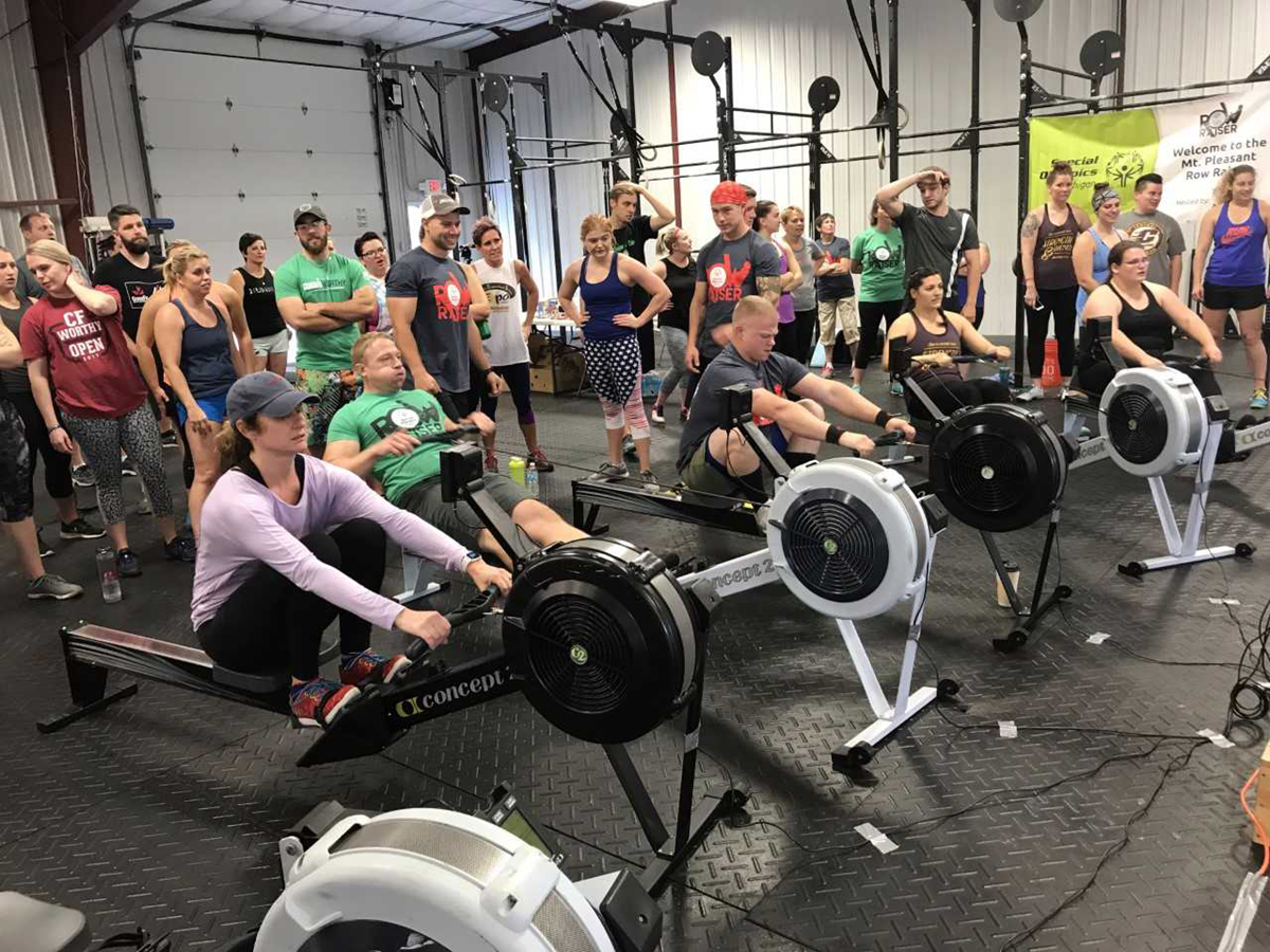 Men and women row on rowing machines